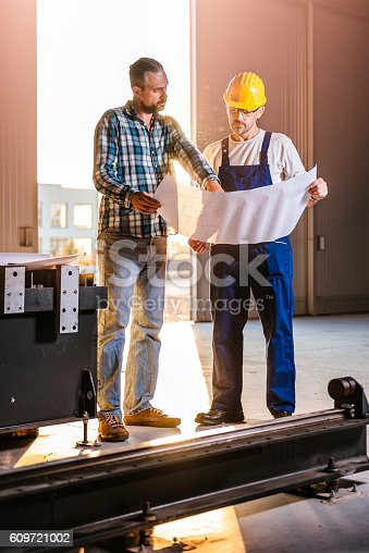 istock Construction workers checking checking blue print 609721002
