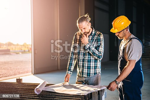 istock Construction workers checking checking blue print 609721128