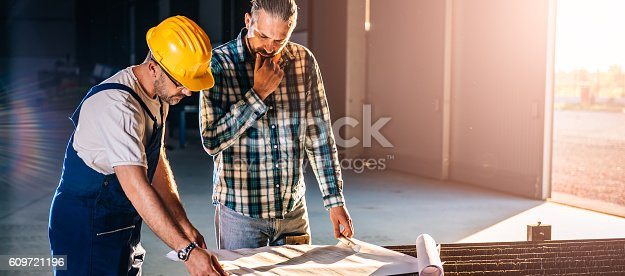 istock Construction workers checking checking blue print 609721196