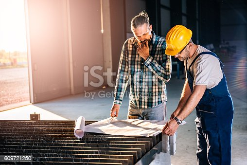 istock Construction workers checking checking blue print 609721250