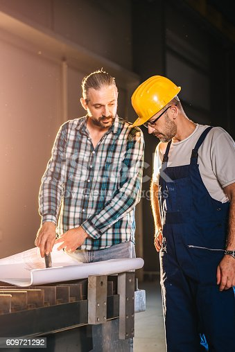 istock Construction workers checking checking blue print 609721292