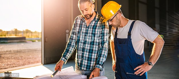 istock Construction workers checking checking blue print 609721352