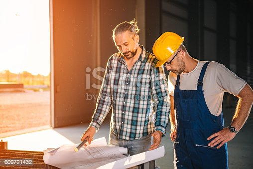 istock Construction workers checking checking blue print 609721432