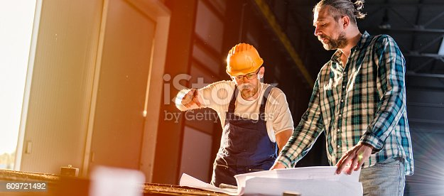 istock Construction workers checking checking blue print 609721492