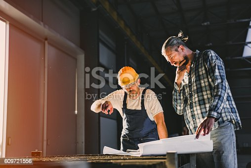 istock Construction workers checking checking blue print 609721556