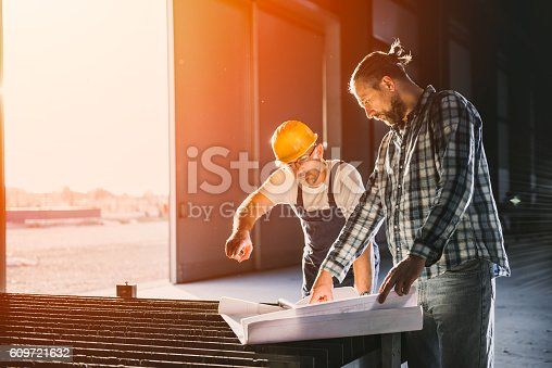 istock Construction workers checking checking blue print 609721632