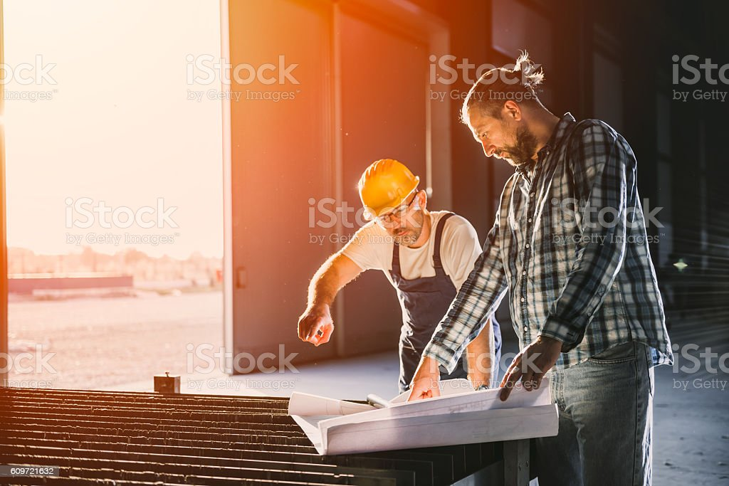Construction workers checking checking blue print - foto de stock