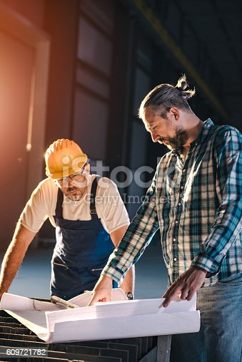 istock Construction workers checking checking blue print 609721782
