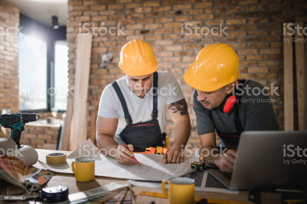 Construction workers cooperating while analyzing housing project in apartment. stock photo