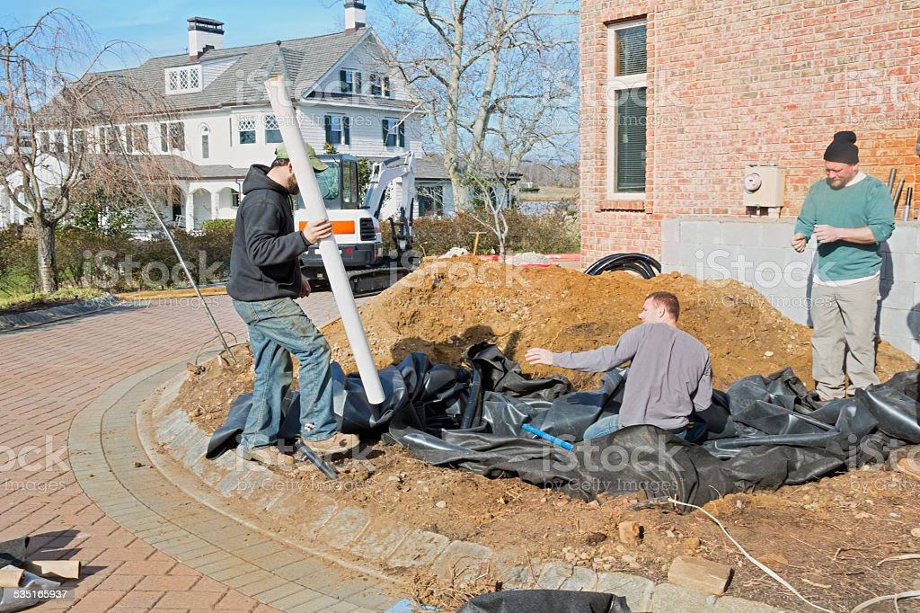 Construction workers digging hole outside residential home stock photo
