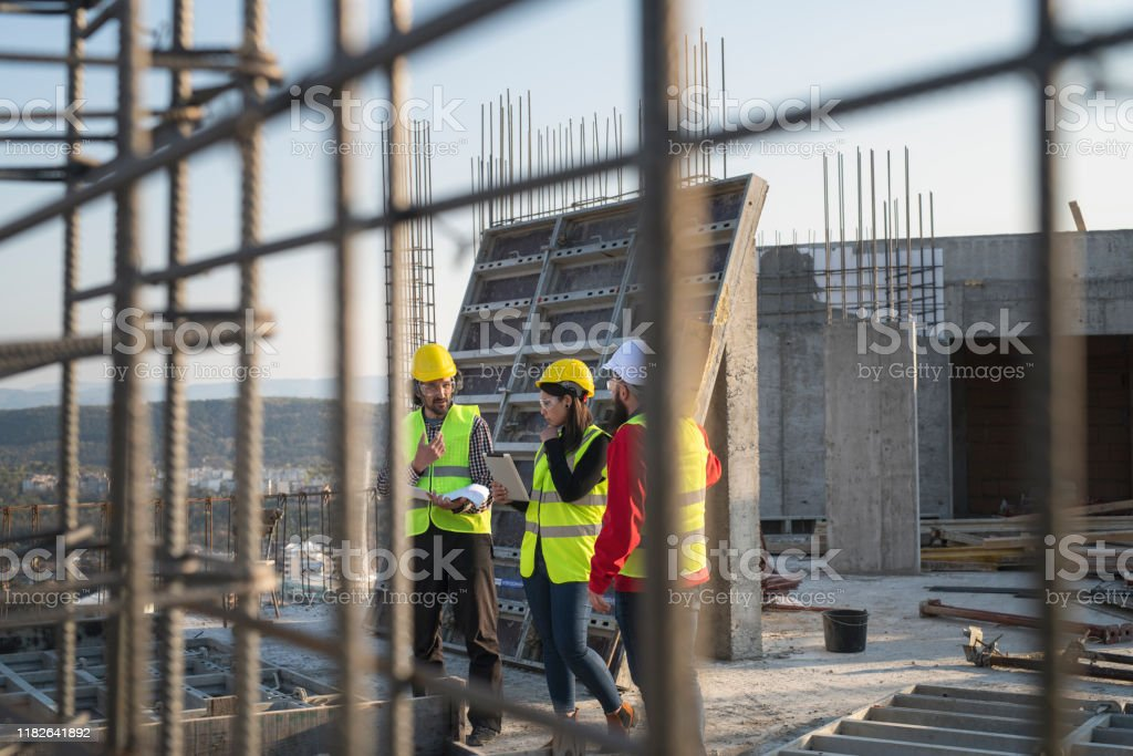 Construction workers discuss the building plans. Construction workers standing on outdoor construction site and discuss the building plans. Adult Stock Photo