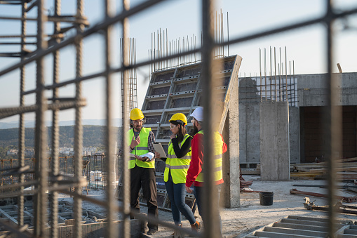 Construction Workers Discuss The Building Plans Stock Photo - Download Image Now