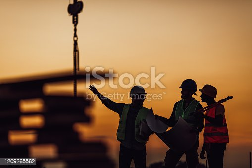 Silhouette of Survey Engineer and construction team working at site over blurred industry background with Light fair Film Grain effect