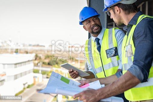 Construction workers talking about new construction site with copy space. Engineers in mechanical factory reading instructions. Architect in construction uniform holding blueprint and discussing.