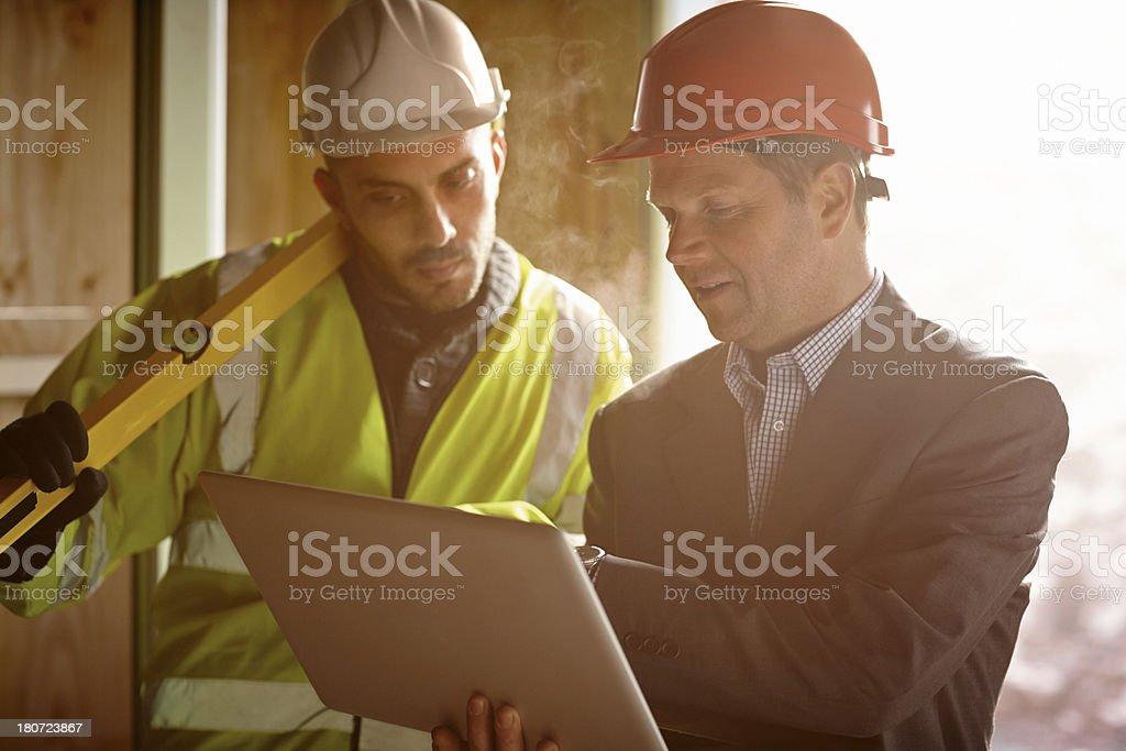 Construction workers examining their plans on a laptop stock photo