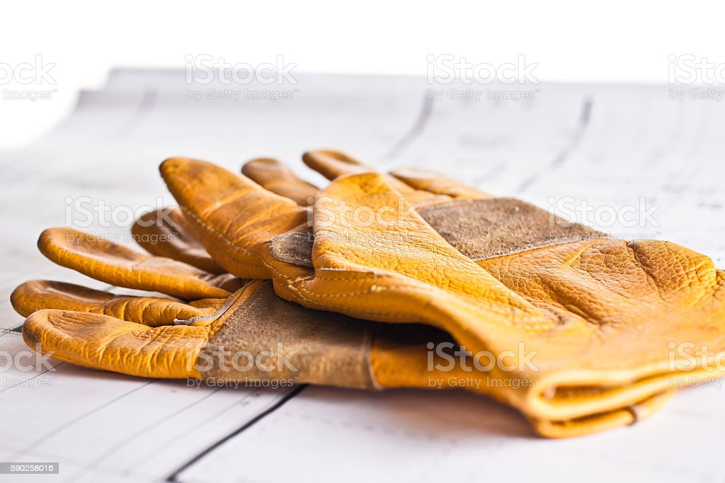 Construction worker's gloves on floorplans. stock photo