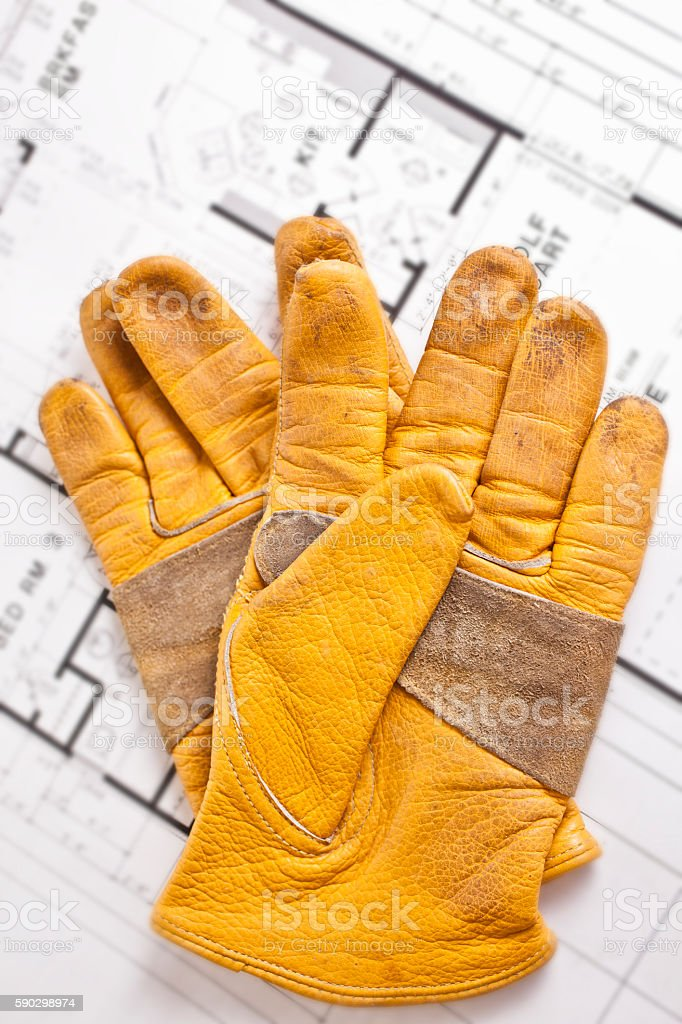 Construction worker's gloves on floorplans. royaltyfri bildbanksbilder