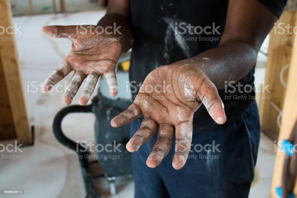 construction worker's hardworking hands on a job site stock photo