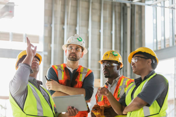 Construction workers having meeting, with digital tablet stock photo