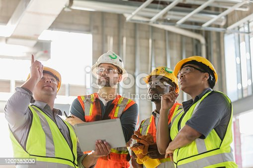 A multi-ethnic group of four construction workers wearing hardhats and safety vests, having a meeting inside the structure being built. A young Hispanic man is holding a digital tablet and pointing up toward the ceiling. The worker on the right is a mature African-American woman in her 40s.
