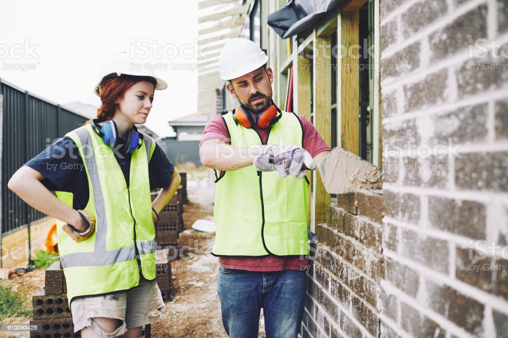 Construction workers in Australian in building site working and doing tasks. stock photo