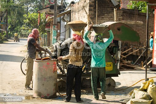November 28, 2019- Kolkata: Men is carrying aggregates bowl on their head. Fellow laborers are working around concrete batch mixer. Everybody is dressed in usual clothes. In background rural home is under construction.