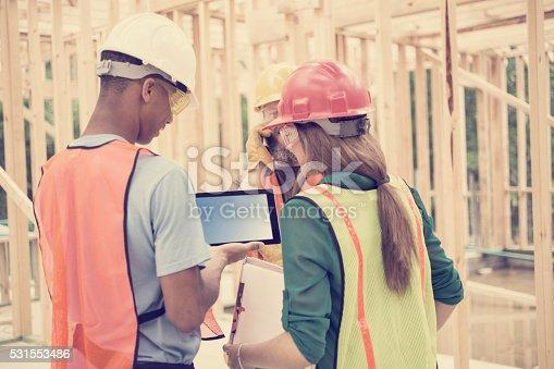 488715470istockphoto Construction workers inside job site. Framed building.  Digital tablet. 531553486