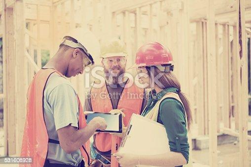 488715470istockphoto Construction workers inside job site. Framed building.  Digital tablet. 531608928