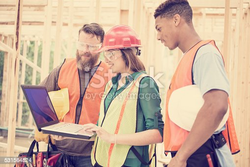 istock Construction workers inside job site. Framed building. Laptop. 531564824