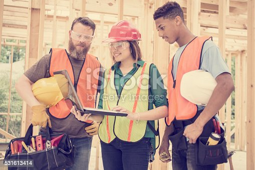 istock Construction workers inside job site. Framed building. Laptop. 531613414
