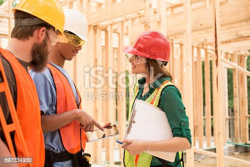 istock Construction workers inside job site using digital tablet. 597234930