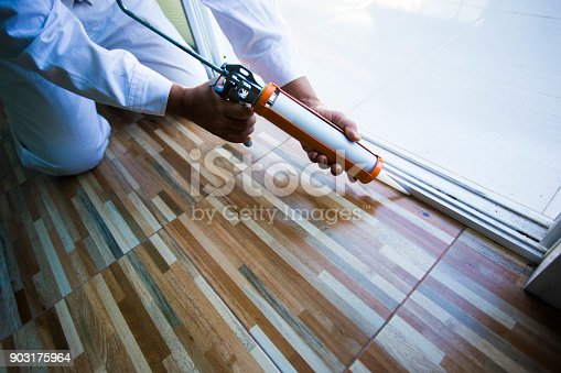 istock Construction workers install doors - windows and use silicon and sealant. 903175964