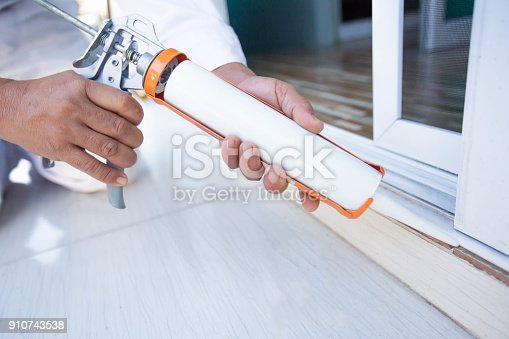 istock Construction workers install doors - windows and use silicon and sealant. 910743538