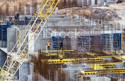 Kharkov, Ukraine - 22 April 2020: Construction workers install formwork and iron rebars or reinforcing bar for reinforced concrete partitions at the construction site of a large residential building.