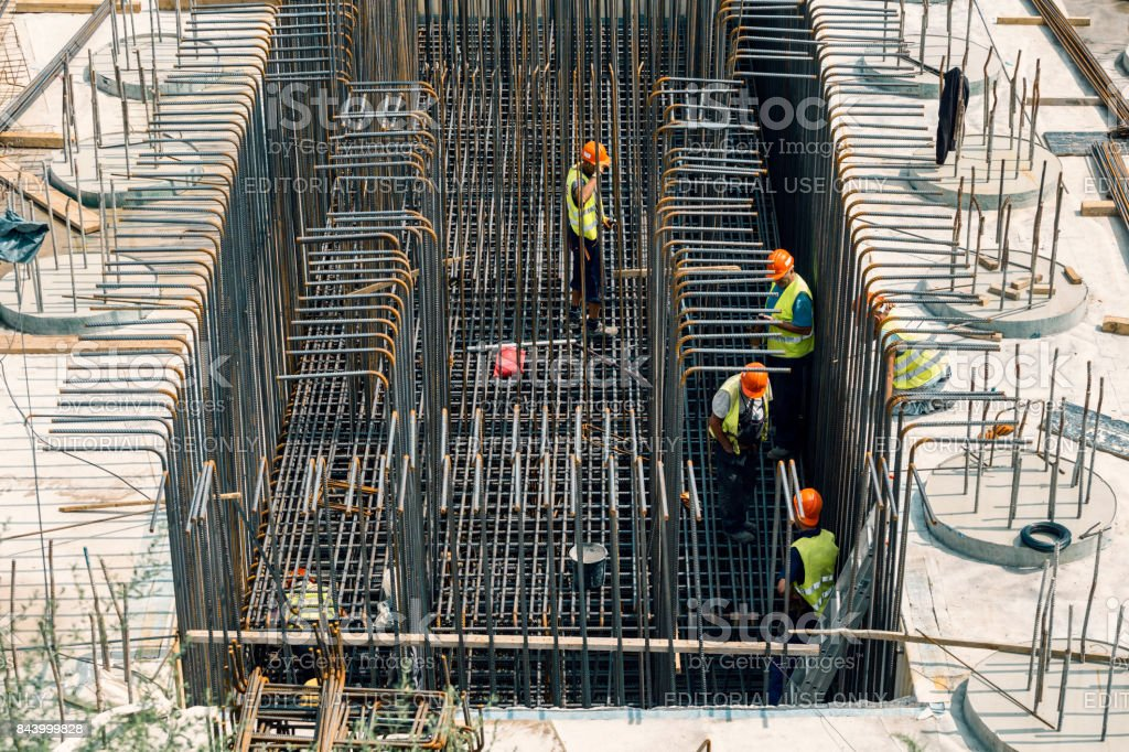 Construction workers install rebar for new building stock photo
