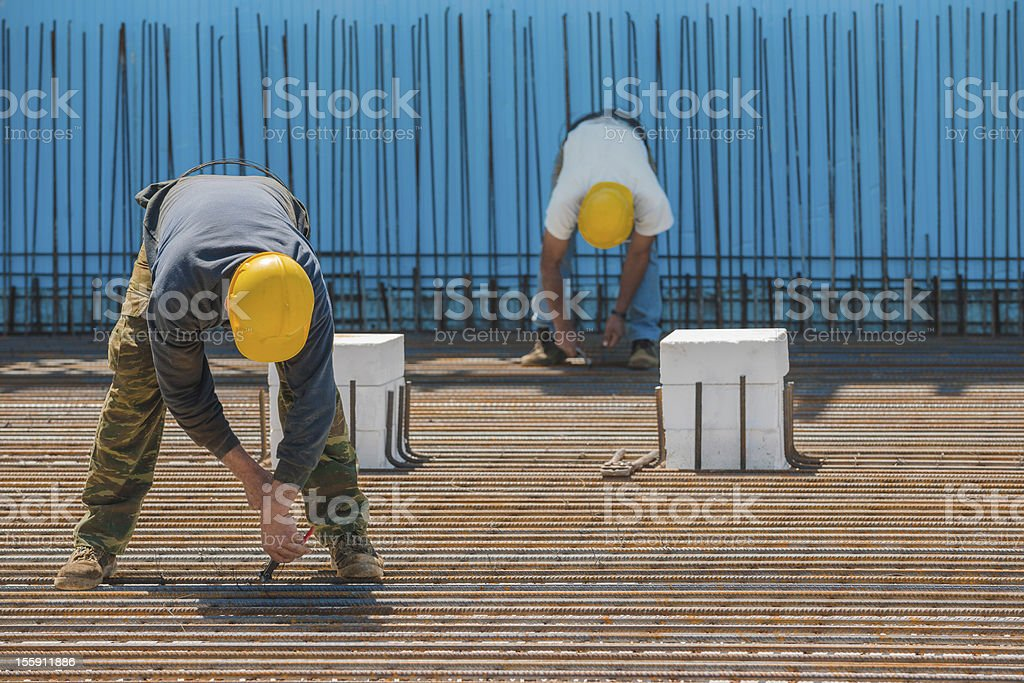 Construction workers installing binding wires to steel bars royalty-free stock photo