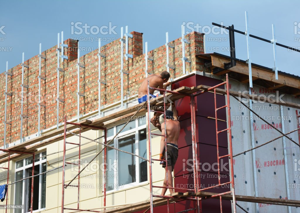 Construction workers insulating house facade with mineral rock wool. External wall insulation system (or EWIS) for energy saving. stock photo