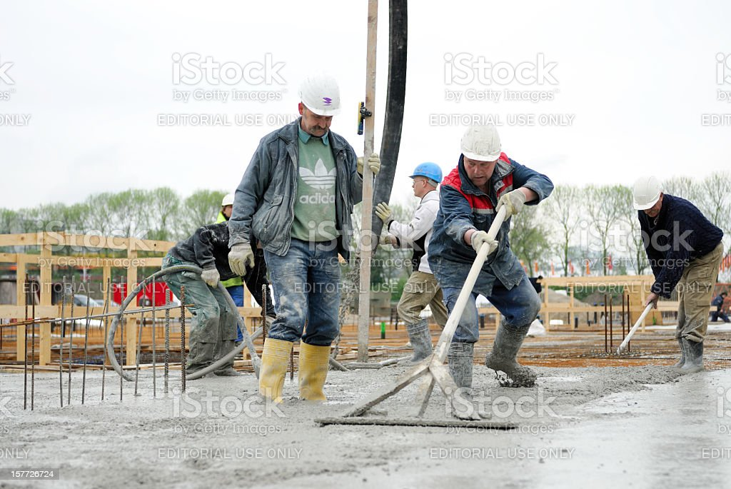 Construction workers laying a building foundation stock photo