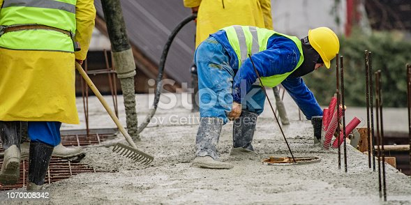 istock Construction workers laying cement on roof 1070008342