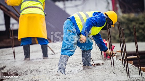 istock Construction workers laying cement on roof 1070008356