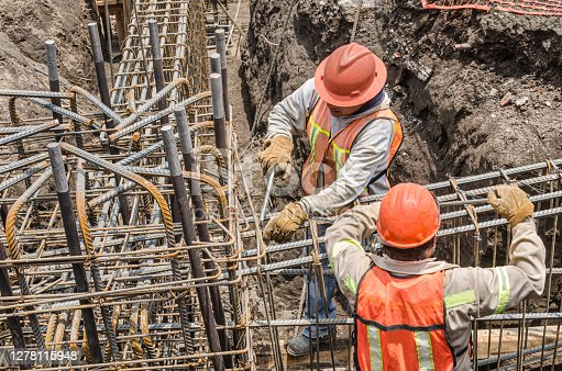 istock Construction workers laying the foundation with iron rods 1278115948