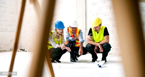 istock Construction workers looking at blueprint on construction site 486821934
