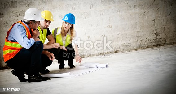 istock Construction workers looking at blueprint on construction site 516047082