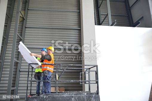 521012560 istock photo Construction workers looking at blueprint on construction site 521012134