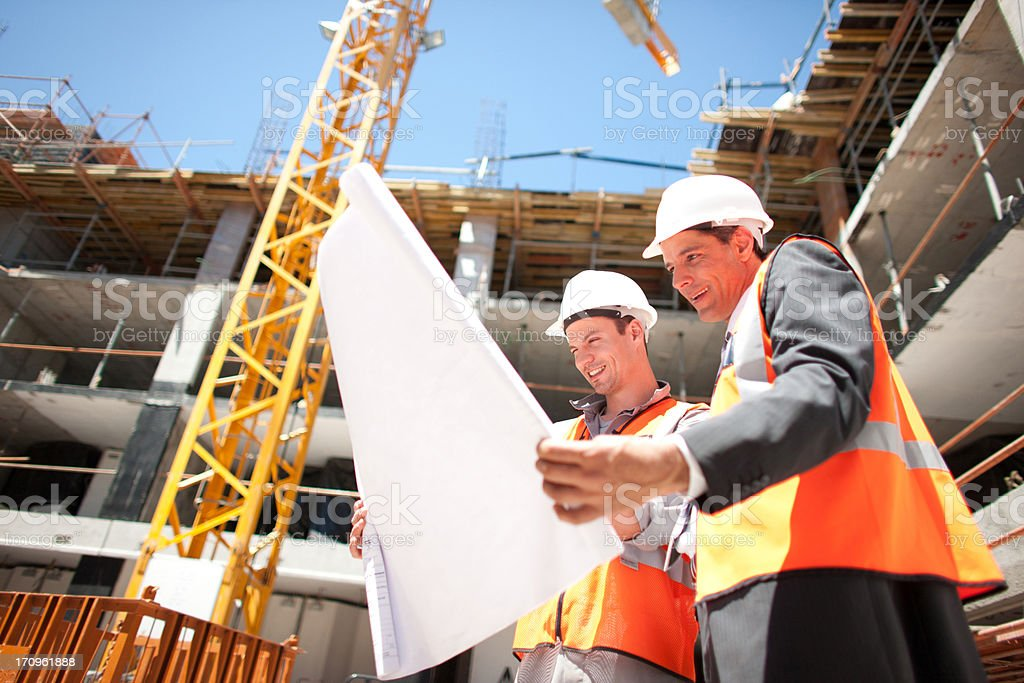 Construction workers looking at blueprints on construction site stock photo