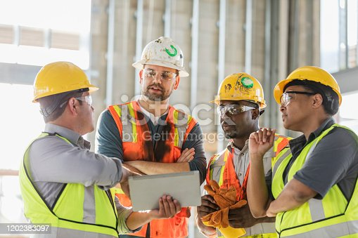 A multi-ethnic group of four construction workers wearing hardhats and safety vests, having a meeting inside the structure being built. A young Hispanic man is holding a digital tablet and they are all looking at the screen. The worker on the right is a mature African-American woman in her 40s.