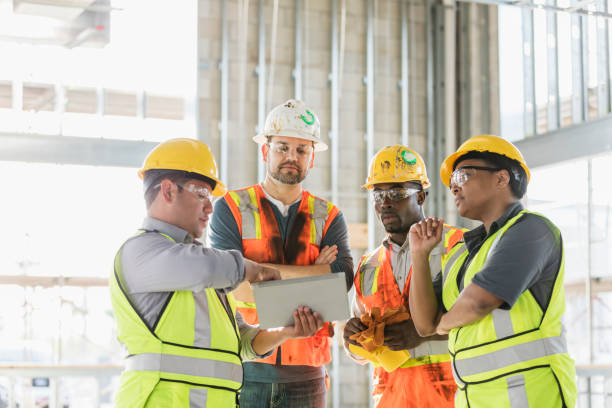 Construction workers looking at digital tablet stock photo