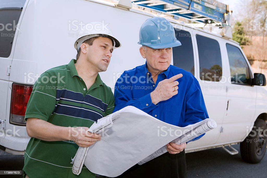 Construction workers looking at plan in front of site royalty-free stock photo