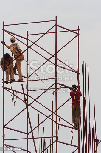 Chennai, India - September 6, 2007: Construction workers on scaffolding in a construction site in Chennai taking minimal safety precautions.