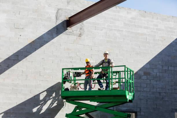 Construction workers on scissor lift stock photo